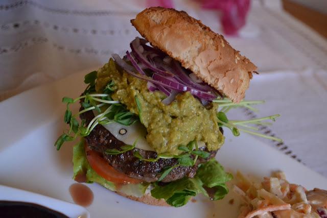 Hamburgertallrik med klyftpotatis och coleslaw serveras med guacamole, pecorinoost och ärtskott (